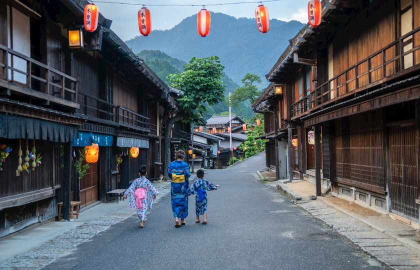 A mother and her children wearing yukata while walking to a local festival