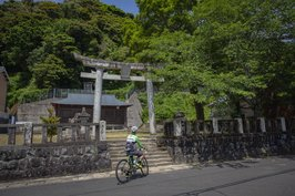 Cycling past a local shrine